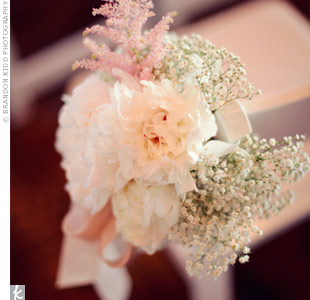 Rustic bunches of garden roses and baby's breath adorned the end chair of each row at the ceremony.