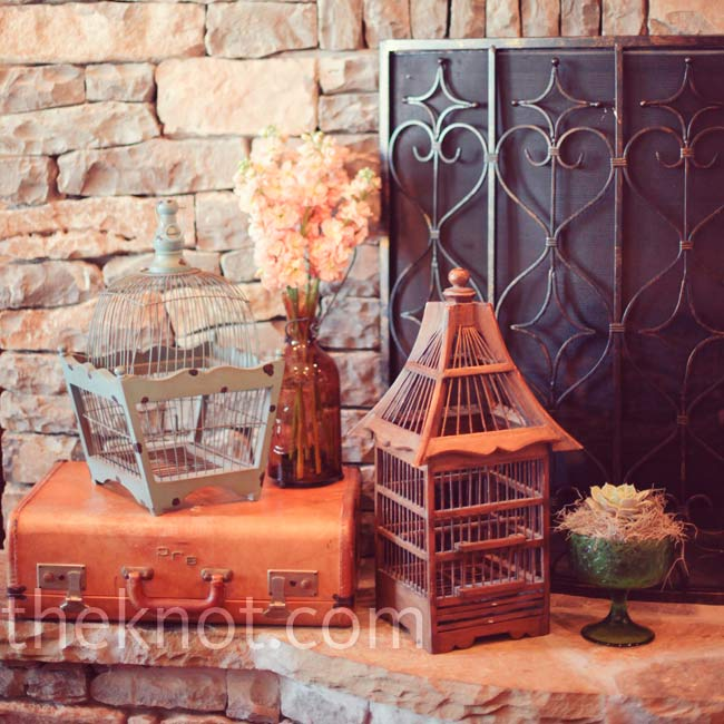Vintage birdcages, vases and suitcases lent an old-world air to the rustic reception venue.