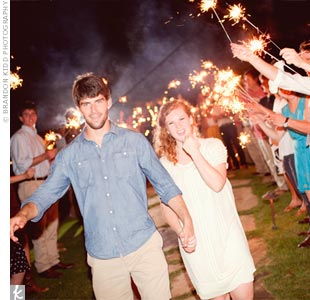 Libby changed into a shorter ivory frock for the couple's escape through a tunnel of sparklers.