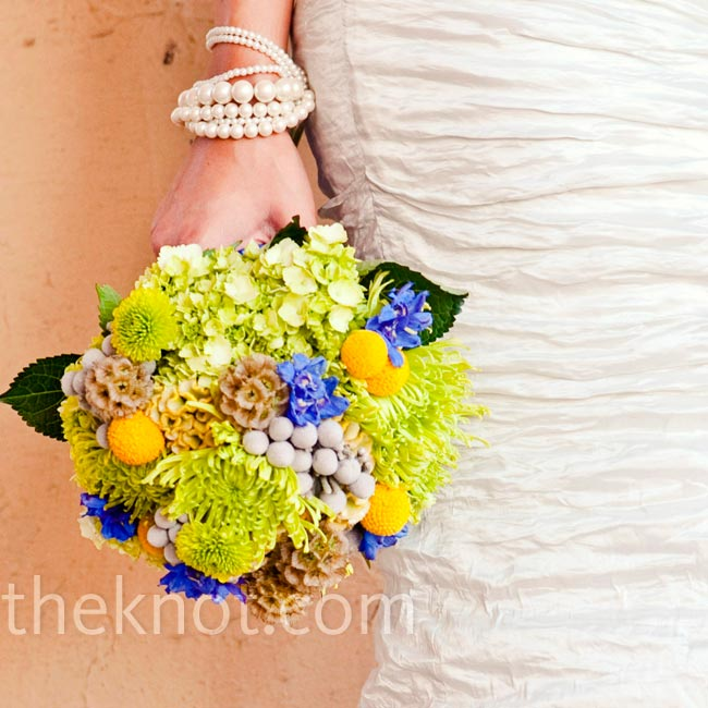 A bouquet of spider mums, hydrangeas, berries and craspedia included all of the wedding colors.