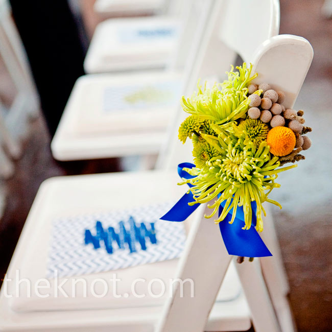 Lime-green spider mums and gray berzelia berries were tied with blue ribbon and hung from aisle chairs.