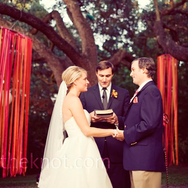 Amy and Matt said their vows beneath a towering oak tree on the venue's grounds. Pink and orange ribbons hanging from the tree marked the altar space.