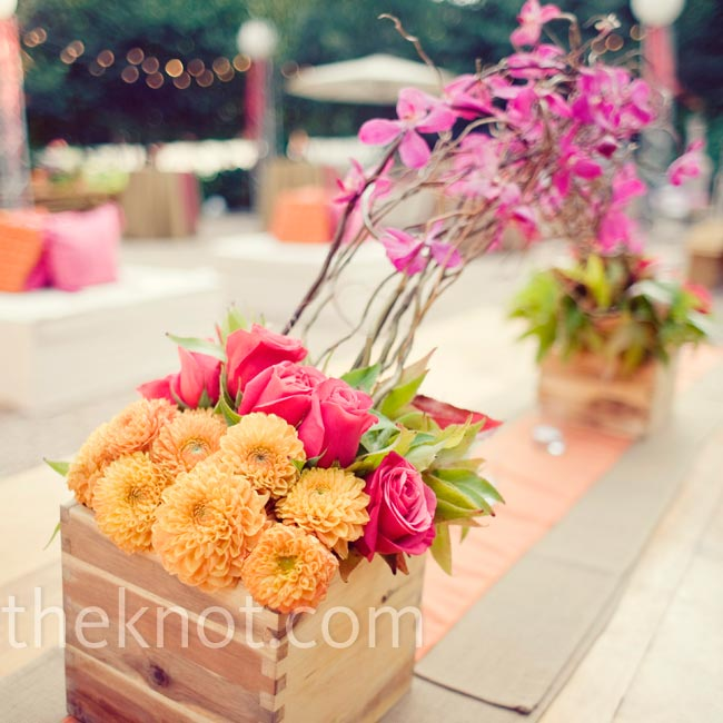 Low boxes filled with orange dahlias and pink roses and orchids decorated the tables, while burlap runners completed the rustic look.