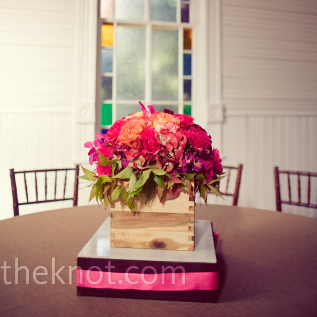 Short, wooden dovetail boxes filled with orange dahlias and pink roses and orchids decorated the reception tables.