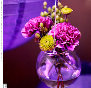 Small glass bowls filled with flowers hung from the couple's ceremony arch.