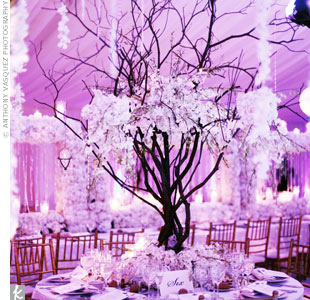 Michael used variety of tablescapes for Danielle and Kevin's wedding: Half of the round tables featured dramatic bare-branch centerpieces, while the other half showcased rounded floral sculptures. Long banquet tables formed the outer edges of the reception space, where Michael had created oversize floral frames.