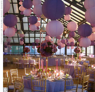 Varied heights and colors of hanging elements, like paper lanterns, add dimension and texture to reception spaces.