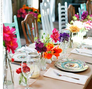 A collection of mismatched Mason jars, vintage vases and antique jars filled with jewel-toned blooms lined the dinner tables.