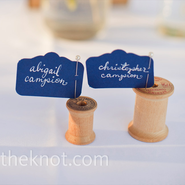 Abigail had her sister calligraph each guest's name onto a navy flag, which she pinned onto spools for the escort cards.