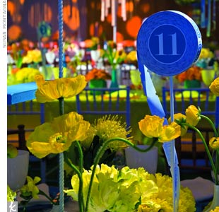 Tablescapes don't have to be stuffy. Get creative with shapes, levels and colors, like this raffle-ticket table number above scattered yellow anemones.