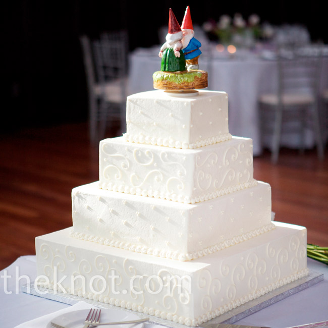 The square buttercream cake was frosted with a simple dot design and topped off with a figurine of two kissing gnomes.