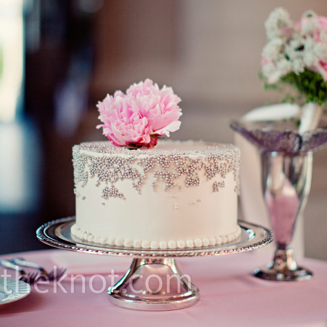 For the cake cutting, the couple's baker made them a small white buttercream cake decorated with silver dragées and a fresh peony.