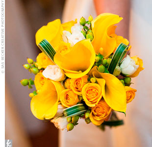 The bridesmaids carried mostly yellow clusters of calla lilies, spray roses, green hypericum berries and loops of lily grass.