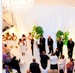 The ceremony setting had floor-to-ceiling fabric as the backdrop. Later, the room was transformed into a party space complete with lighting and a mirrored bar.