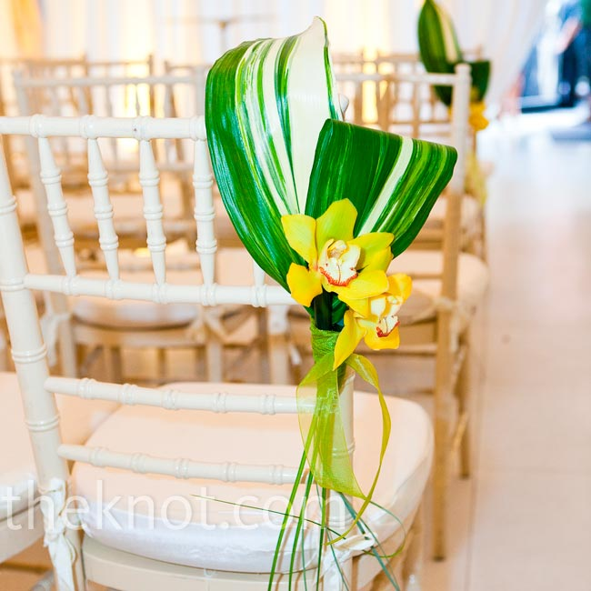 Folded flax leaves with a couple of cymbidium orchids decorated every other aisle seat.