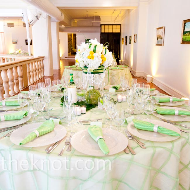 Muted green linens and mostly white centerpieces fit well with the venue's natural lighting.