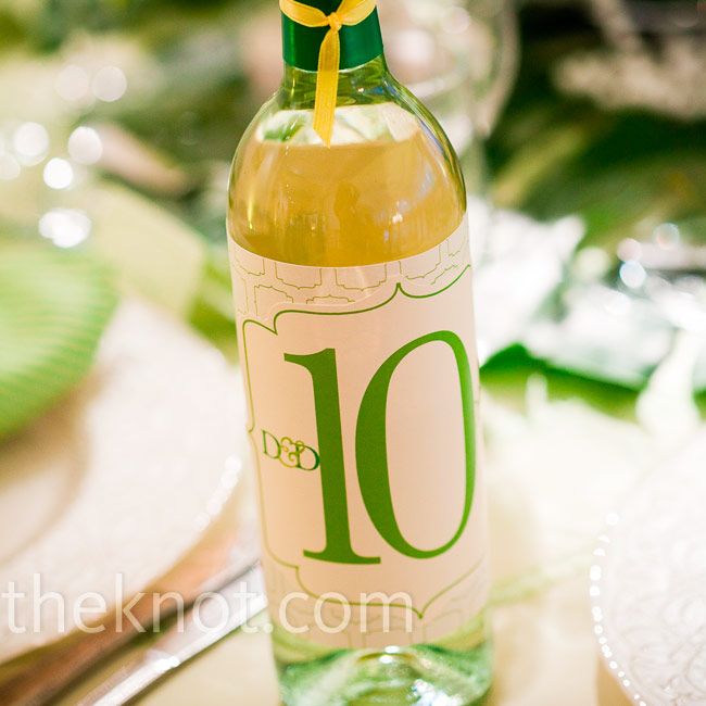 Wine bottles labeled with the table numbers and the couple's custom monogram marked each table.