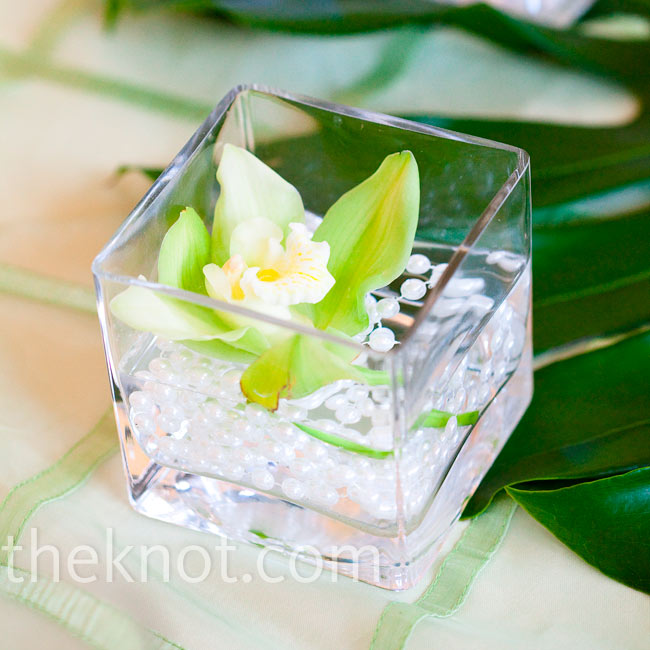 Along with centerpieces, square glass vases filled with orchids and pearls decorated each table.