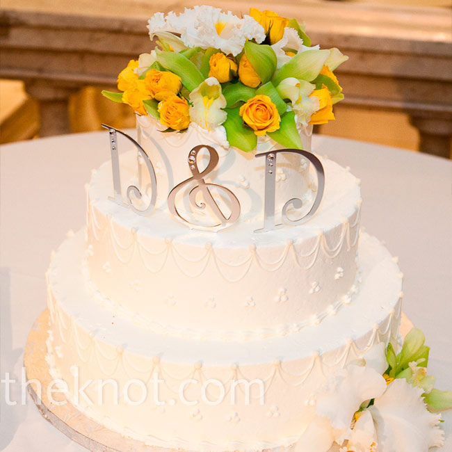 Sleek monogram letters and fresh orchids adorned the top tier of the simple all-white cake.