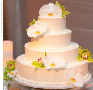 Fresh lilies and orchids decorated the four-tiered white buttercream cake.