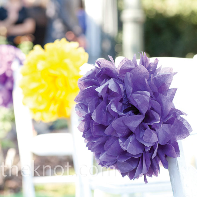 The bride added bursts of purple and yellow to the wedding aisle with large tissue paper pompoms.