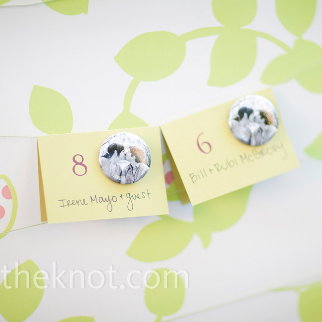 The couple attached custom photo buttons to the escort cards and displayed them on a bulletin board.