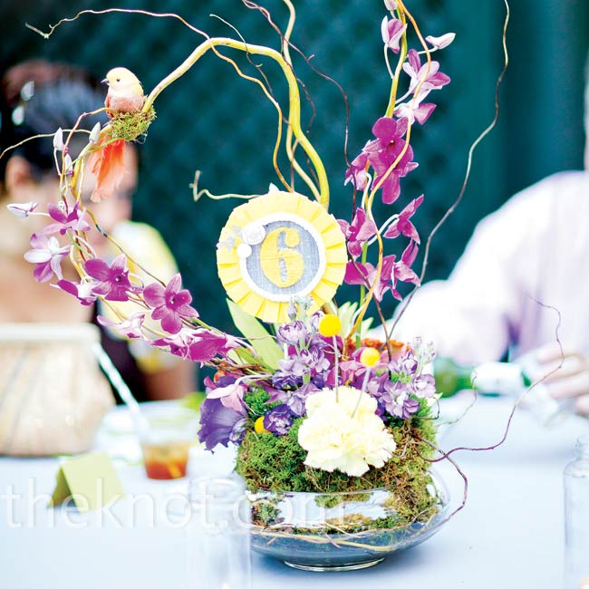 Curly branches, purple orchids and pops of yellow craspedia sprouted from beds of moss and succulents. Little birds perched atop each arrangement, tying together the theme of the day.