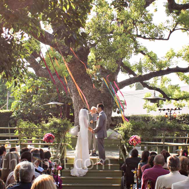 The ceremony took place beneath a 200-year-old tree in the center of the venue. Long jewel-toned ribbons hung from the branches.