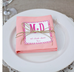 Coral napkins and fuchsia napkin cards wrapped with twine added color to the simple white china.