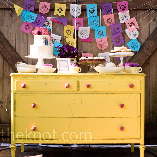 The couple spruced up a vintage dresser for their dessert buffet table. The cake and cupcakes were displayed on dishware that had been passed down from Maya's grandparents.