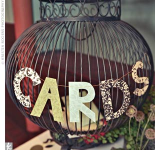"Guests dropped cards into a metal birdcage decorated with garland spelling out ""cards"" on the gift table."