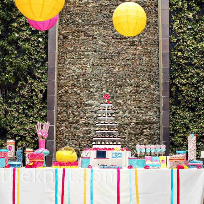 A candy bar filled with assorted blue, yellow and pink sweets like gumballs, saltwater taffy and lollipops fit the theme. Ribbons hanging from the table added even more color.
