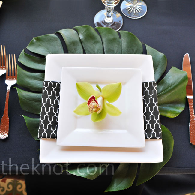 Square plates and black-and-white napkins gave the tables a mod look. The leaf placemats beneath were an unexpected addition.