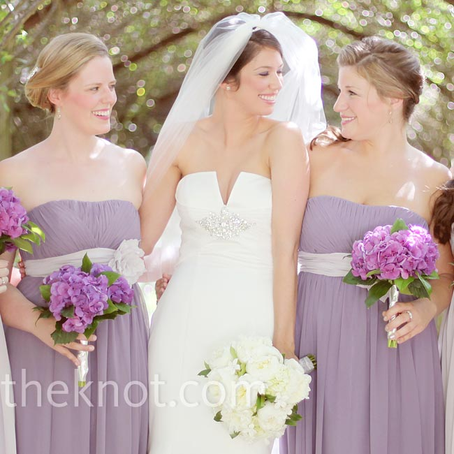 The bride had fun with the colors in the bridesmaids' dresses, choosing three lavender chiffon gowns with gray sash details and two others with the opposite color scheme.