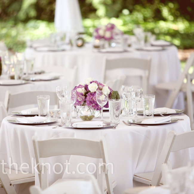 Purple hydrangeas and white roses spilled from glass bowls in the middle of each white linen-covered table. White napkins stood out against silver chargers at each place setting.