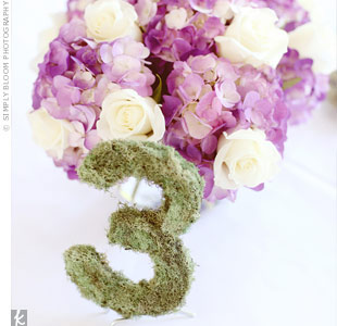 Wooden table numbers covered in dried moss stood out against the white linens and fit right in with the garden surroundings.