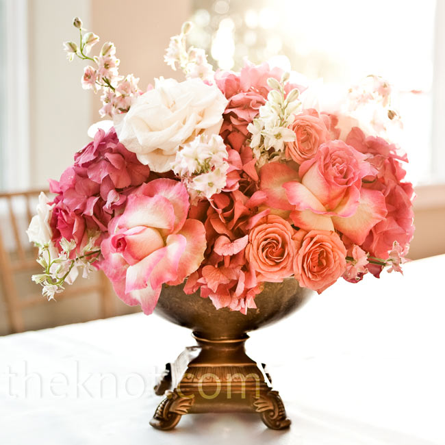 Brushed-gold urns held gorgeous arrangements of pink roses and hydrangeas in varying heights to give the room depth.