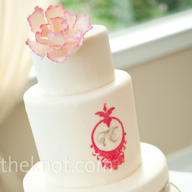 An elegant pink sugar flower topped the white wedding cake embellished with a silver monogram in a hot pink frame of sugar.