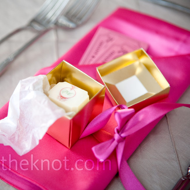 Guests found gold boxes tied with pink bows on their reception chairs. Inside were two pieces of monogrammed chocolate.