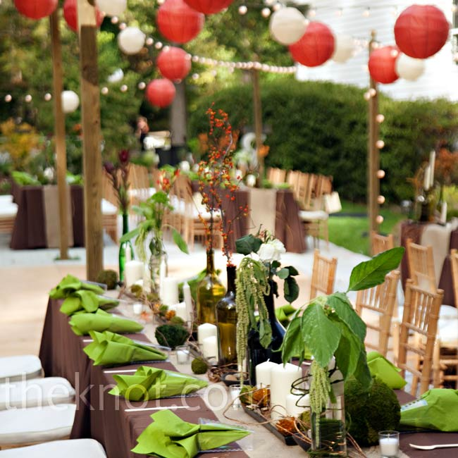 Single stems of bells of Ireland, dried berries, orange freesia or bear grass sprouted from wine bottles on each table.