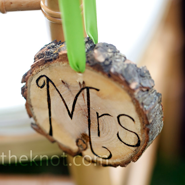 """Mr."" and ""Mrs."" were burned into small slices of trunk and hung with green ribbon from the couples' reception chairs."