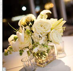 Lower centerpiece arrangements of roses and stephanotis contrasted against the tall centerpieces, giving the large reception space some depth.