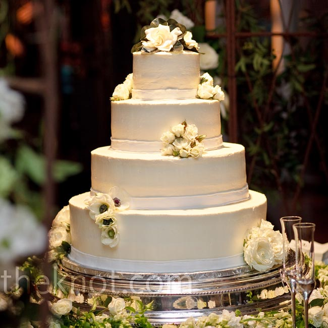 The four-tiered cake was iced with white buttercream and adorned with white and black anemones and white roses.
