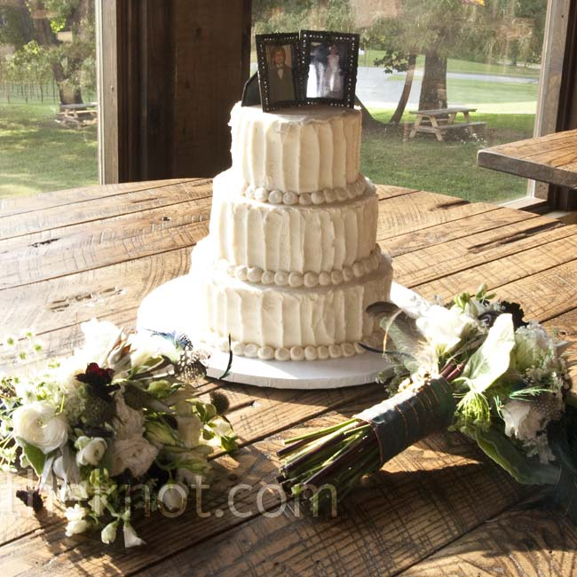 The bride and groom cut into a textured cake with alternating tiers of buttercream and cream cheese icing. Their photos topped off the confection.