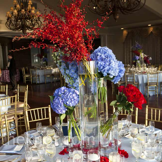 Cylinder vases of varying heights were filled with clusters of red or blue blooms, like delphiniums, orchids and hydrangeas.