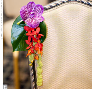 Chairs along the aisle were decorated with tiny monstera leaves, vanda and amaranthus orchids.