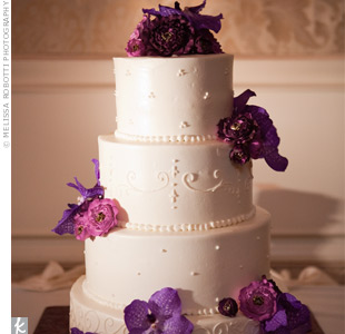 A mix of sugar flowers and fresh orchids decorated the white-on-white cake.