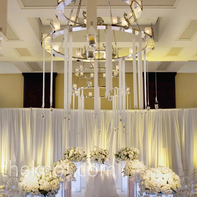 LED-lit pedestals topped with white flowers lined the aisle, while a chandelier with hanging votives created an ethereal atmosphere.