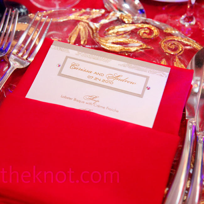 Menus embellished with Swarovski crystals and bright-red napkins rested atop clear and gold glass chargers.
