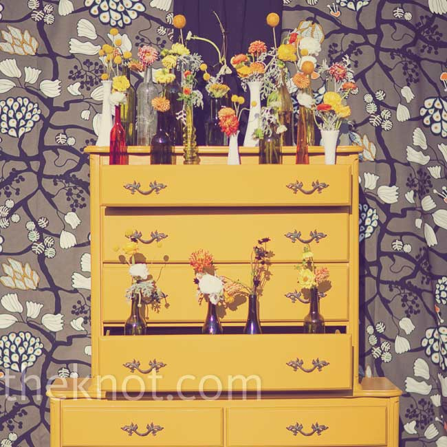 Lesley and Mike made their vintage ceremony backdrop by nailing two old dressers together and painting them a mustard color. They filled the drawers with flowers in mismatched vases.